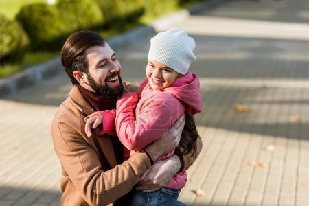 happy father with daughter hugging. outside