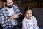 father making braids to daughter at home