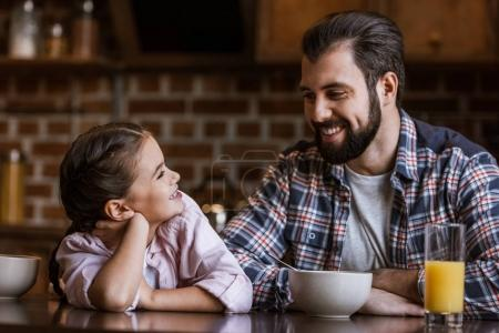 happy father with daughter sitting at table with juice and bowls and looking at each other at kitchen
