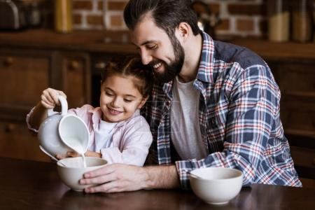 father and daughter pouring milk in bowl with snacks at kitchen