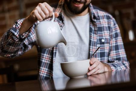 cropped image of man pouring milk in bowl with snacks at kitchen