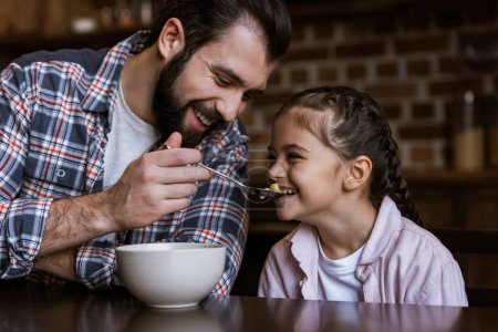cheerful family at table, father feeding daughter by snacks with milk at kitchen