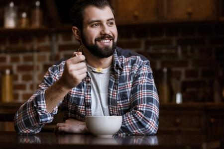 smiling man eating snacks with milk at kitchen