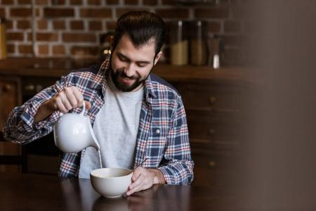 handsome man pouring milk in bowl with snacks at kitchen