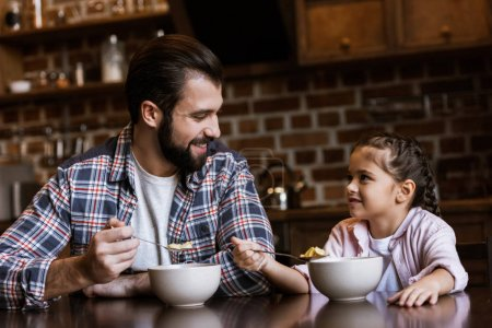 cheerful father and daughter sitting at table and eating snacks with milk at kitchen