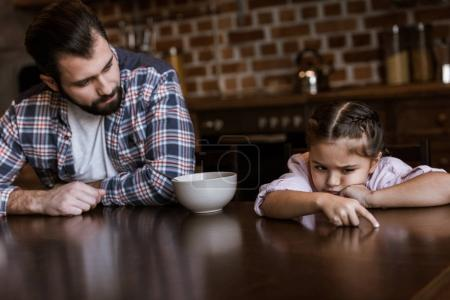 father with daughter sitting at table, little kid dont want eat breakfast at kitchen