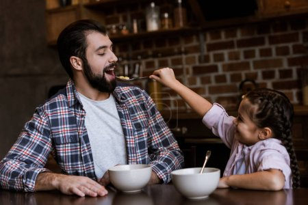 cheerful family at table, daughter feeding father by snacks with milk at kitchen