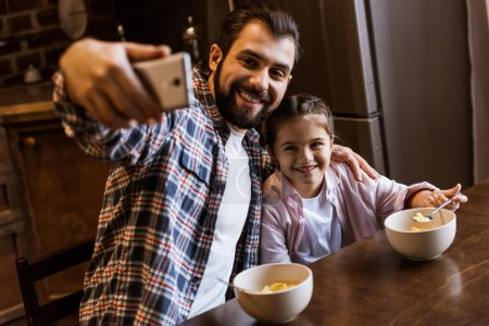 happy father with daughter sitting at table with snacks in bowls and takes selfie at kitchen