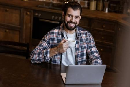 handsome man with coffee cup sitting at table with laptop