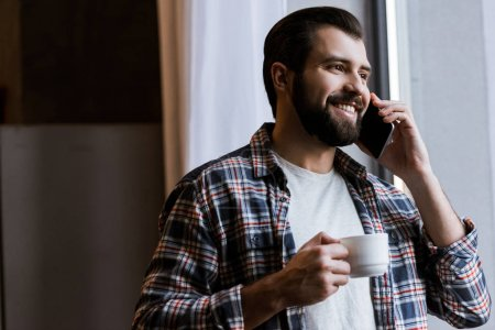 happy man holding coffee cup and speaking on smartphone at home