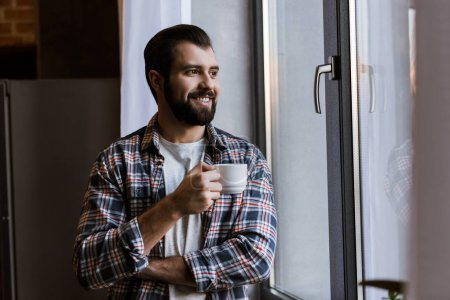 happy handsome man with coffee cup looking at window