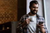happy man holding coffee cup and using smartphone at home