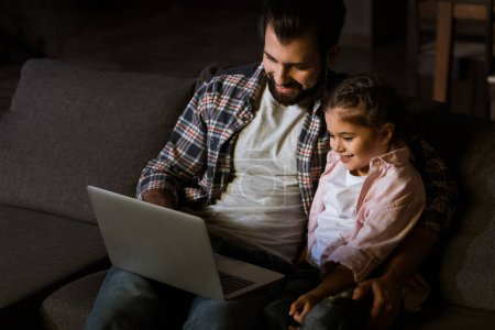 cheerful father with daughter sitting on couch and using laptop