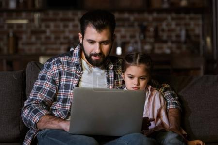 father with daughter sitting on couch and using laptop