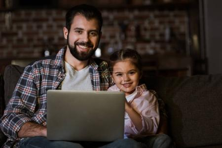 happy father with daughter sitting on couch and using laptop