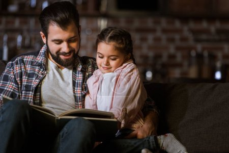 Photo for Happy father with daughter hugging on couch and reading book at home - Royalty Free Image