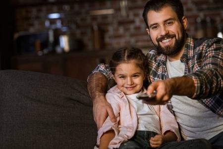 Photo pour Heureux père avec sa fille assise dans le canapé, embrasser et regarder la télévision à la maison - image libre de droit