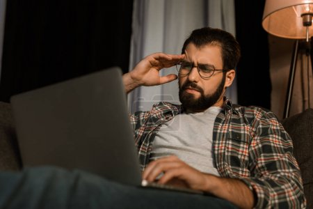 tired man in glasses sitting on couch with laptop