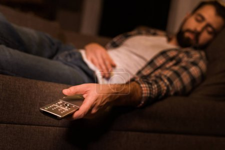 Photo for Young tired man fall asleep on couch with TV remote control in hand at home - Royalty Free Image