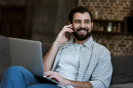 handsome man sitting on couch with laptop and speaking on phone