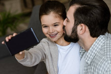 cheerful father with daughter taking selfie on smartphone at home