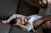 father with daughter laying on couch, hugging and laughing at home