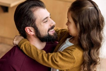 portrait of father and daughter hugging and looking at each other