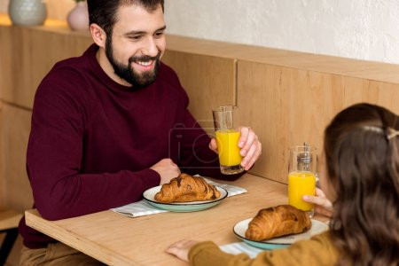 father and daughter drinking orange juice in cafe