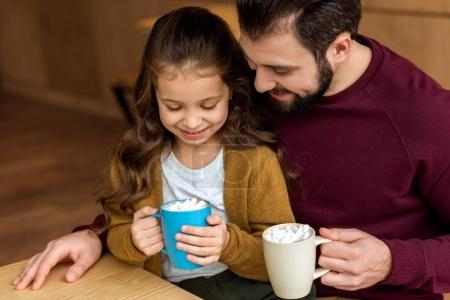 adorable daughter sitting on father knees and holding cup of cacao with marshmallow and looking down