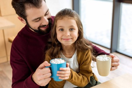 adorable daughter sitting on father knees and holding cup of cacao with marshmallow and looking at camera