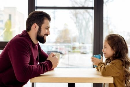 happy father and daughter holding cups in cafe and looking at each other