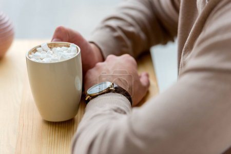 cropped image of man holding cup of coffee with marshmallow