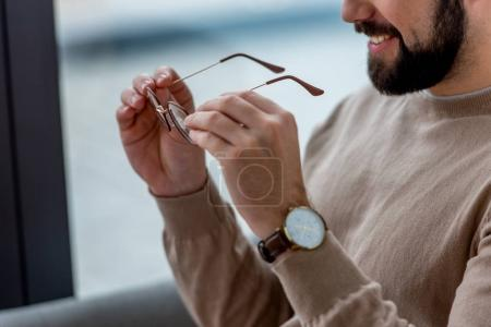 Photo for Cropped image of smiling man holding glasses - Royalty Free Image