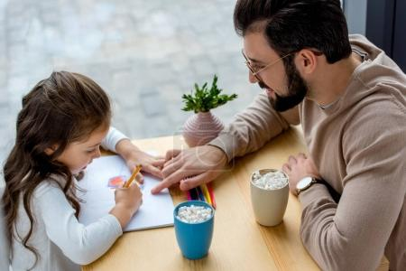 cheerful father showing daughter where to draw