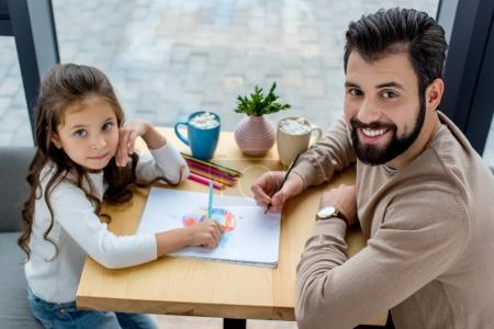 père et fille rapprochant et en regardant la caméra