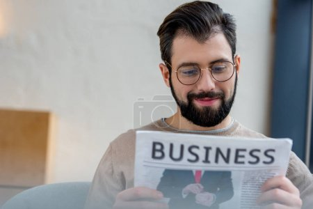 Smiling man reading business newspaper