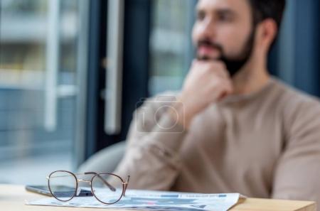 Photo pour Homme pensif assis dans le café avec des lunettes sur le premier plan - image libre de droit