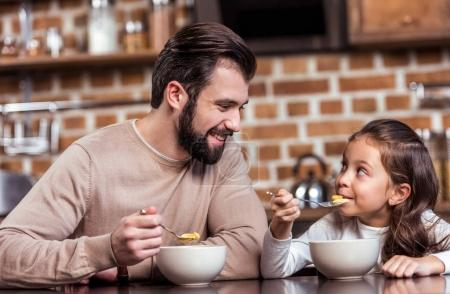 smiling father and daughter eating breakfast and looking at each other