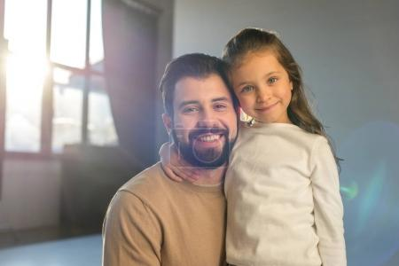 smiling father and daughter posing in room and looking at camera