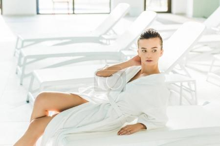 attractive young woman in bathrobe relaxing on sunbed at spa