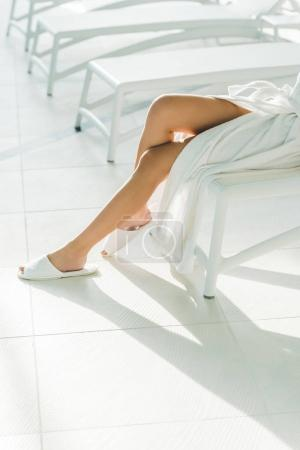 cropped shot of woman in bathrobe and slippers relaxing at spa