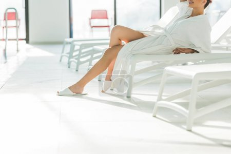 cropped shot of attractive young woman in bathrobe lying on sunbed at spa