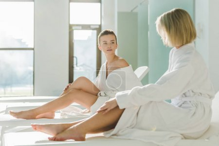 attractive young women sitting on sunbeds at spa center and talking