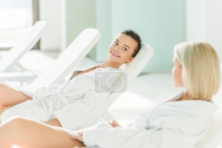 happy young women relxing on sunbeds at spa center