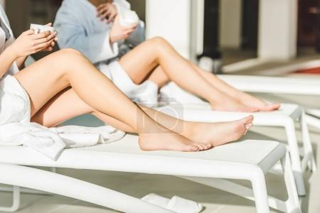 cropped shot of women with beautiful legs drinking coffee at spa center while sitting on sunbeds