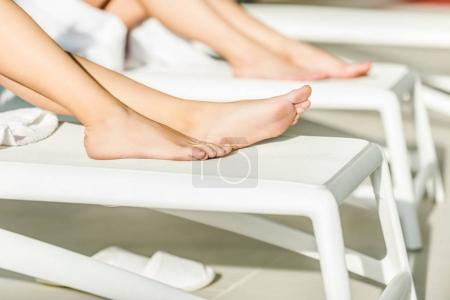 cropped shot of beautiful young women lying on sunbeds at spa center