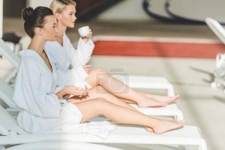 attractive young women drinking coffee at spa center while sitting on sunbeds