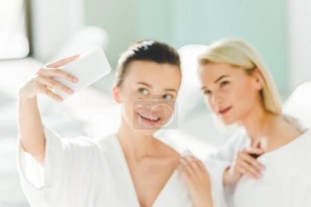 happy young women in bathrobes taking selfie at spa center