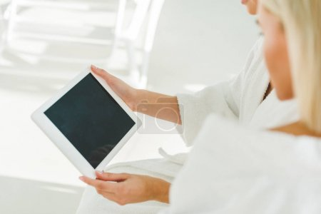 cropped shot of young women using digital tablet at spa center