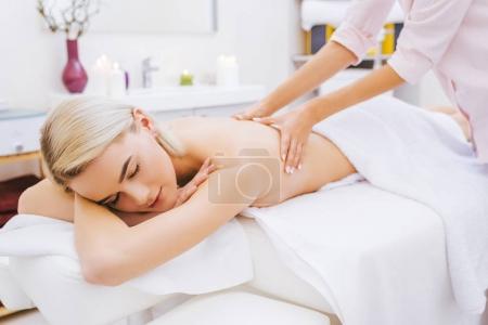 Photo pour Belle jeune femme se faire masser le dos au spa salon - image libre de droit